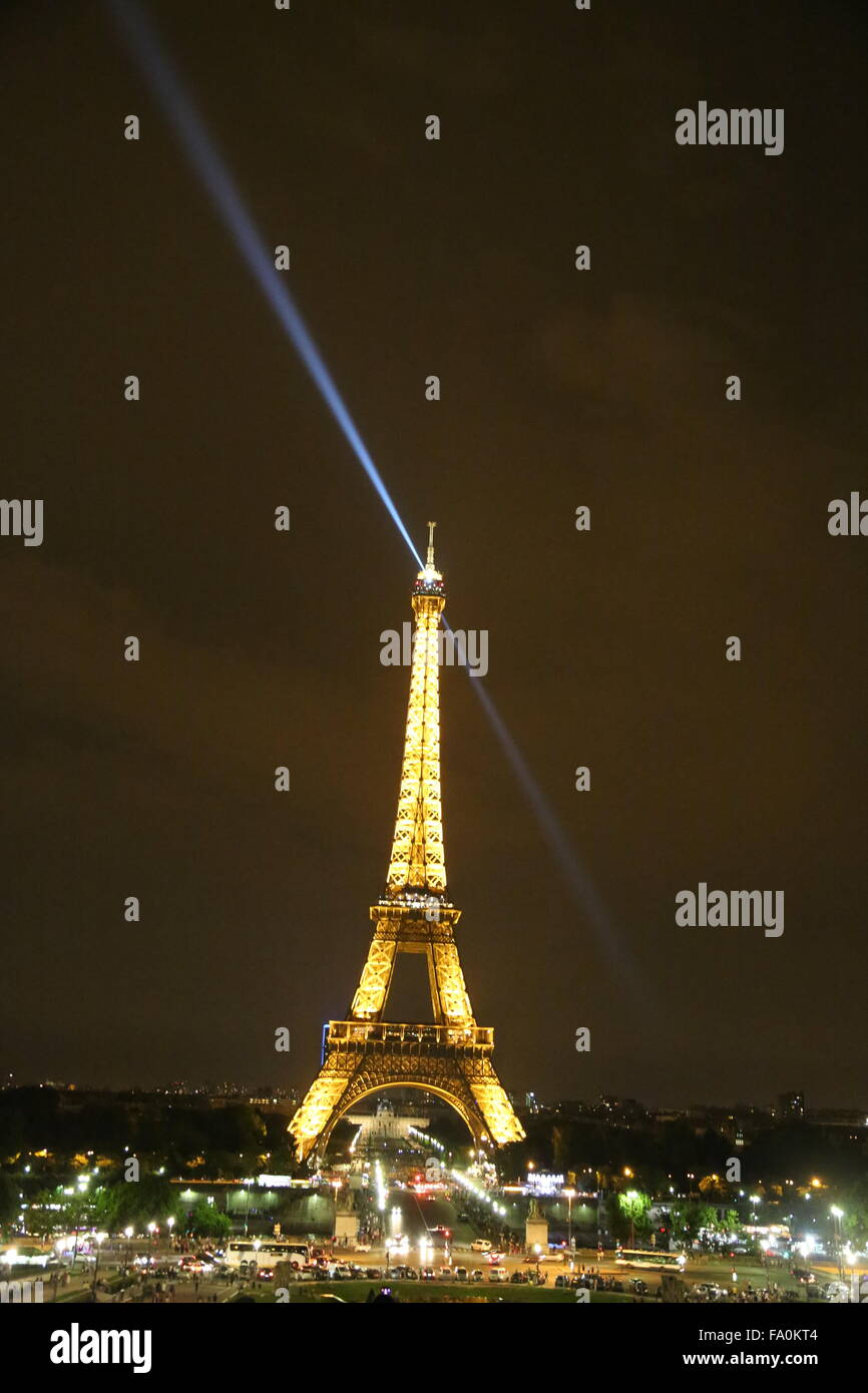 The Eiffel Tower at night with the search light at the tip of the tower trailed diagonally in the background, and - Stock Image