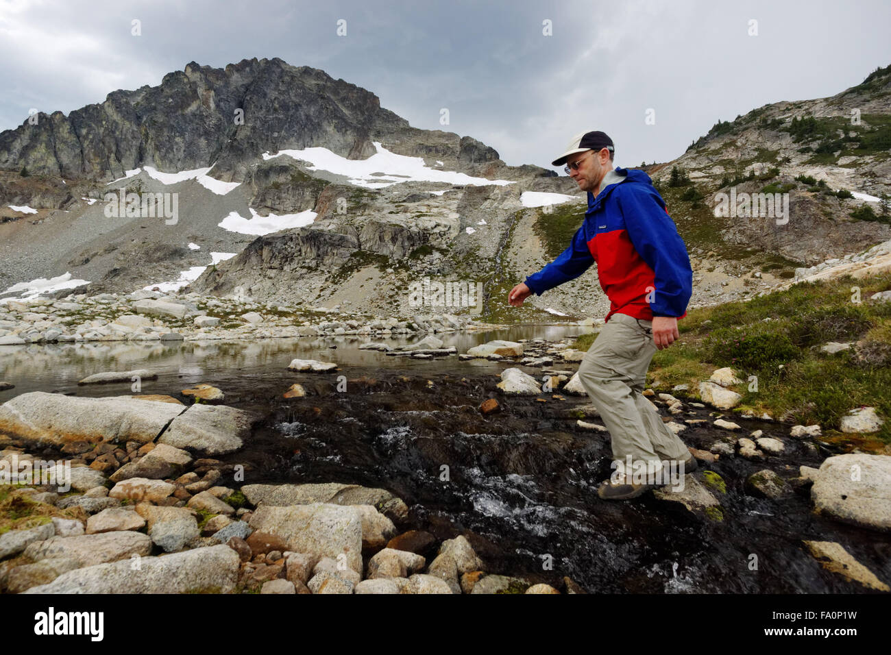 Man leaping stream, Silent Lakes, North Cascades National Park, Skagit County, Washington, USA - Stock Image