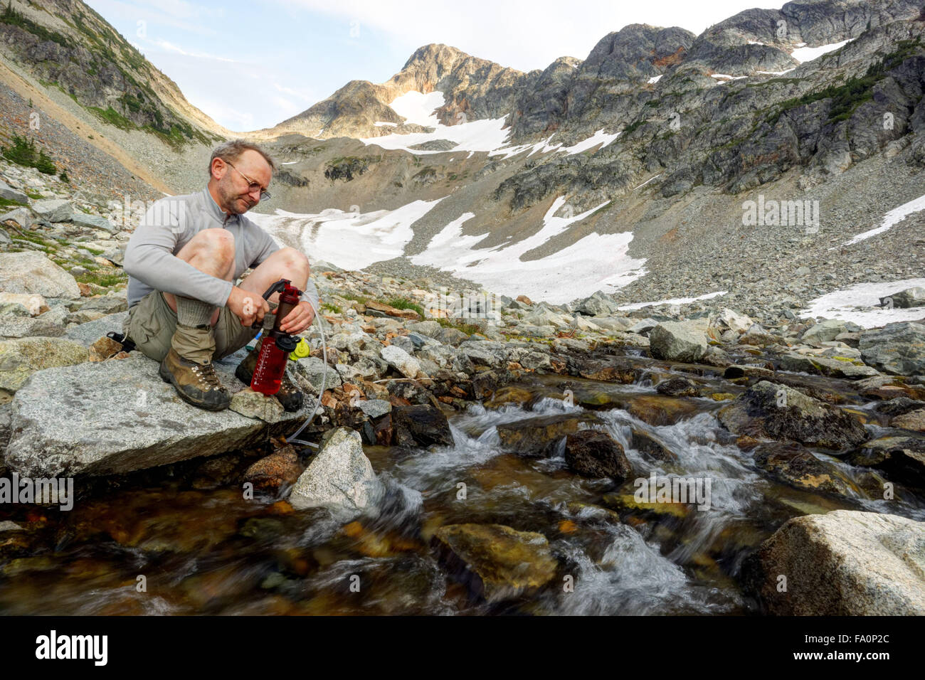 Man pumping water from Fisher Creek, Fisher River Basin, North Cascades National Park, Skagit County, Washington, - Stock Image