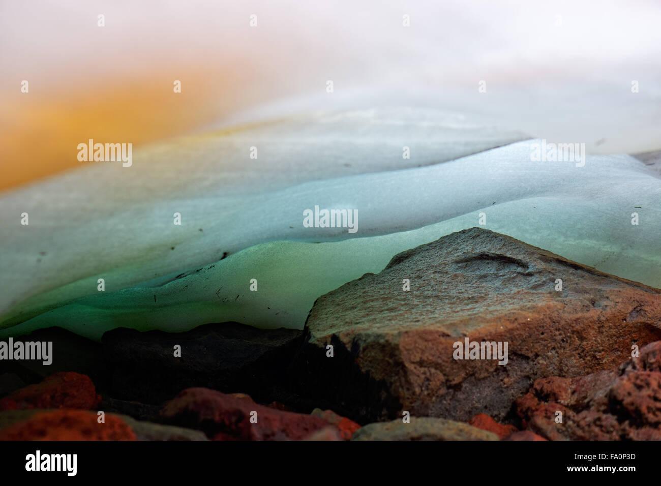 Underside of snowfield melting onto rocks, Spray Park, Mount Rainier National Park, Washington State, USA - Stock Image