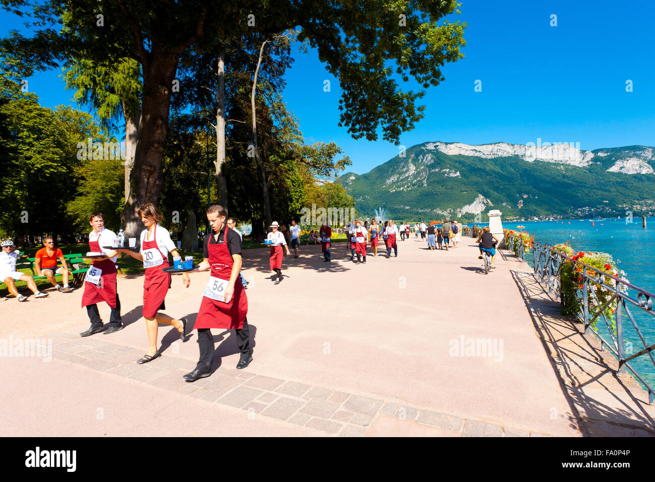 Many waiters wearing red aprons running with loaded trays around Annecy Lake at the French Alps during the Waiter's - Stock Image
