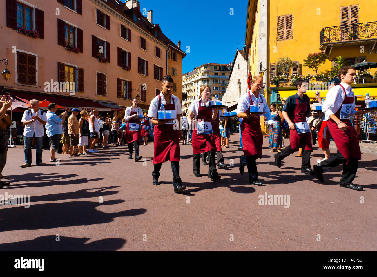Professional waiters wearing red aprons carrying, balancing loaded trays of liquid while running around Annecy old - Stock Image
