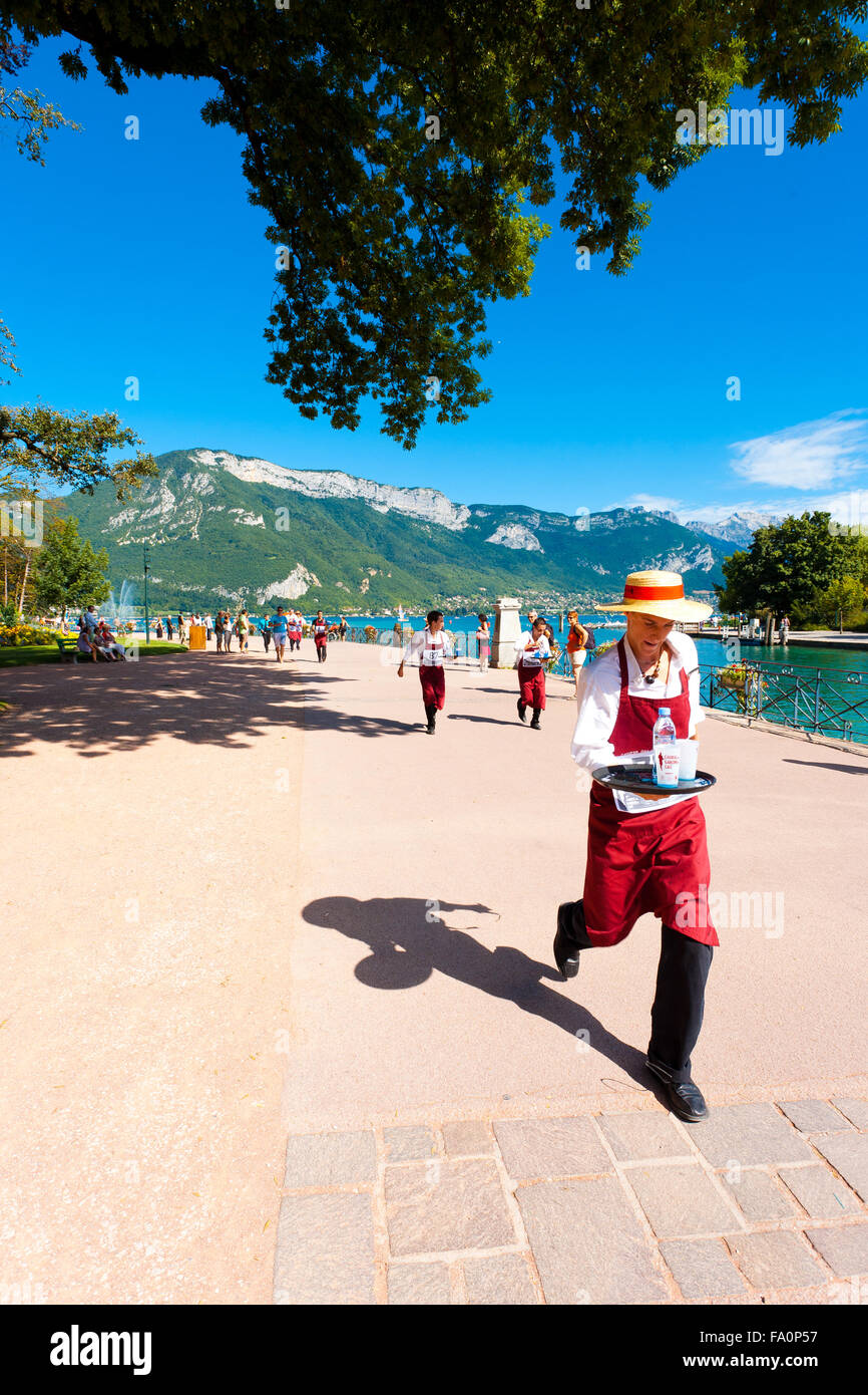 An apron wearing waiter runs with a loaded tray around Annecy Lake at the French Alps during the Waiter's Race - Stock Image