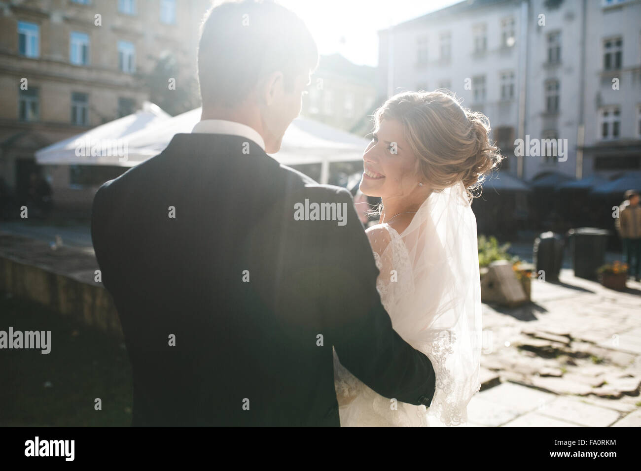 bride and groom posing on the streets - Stock Image