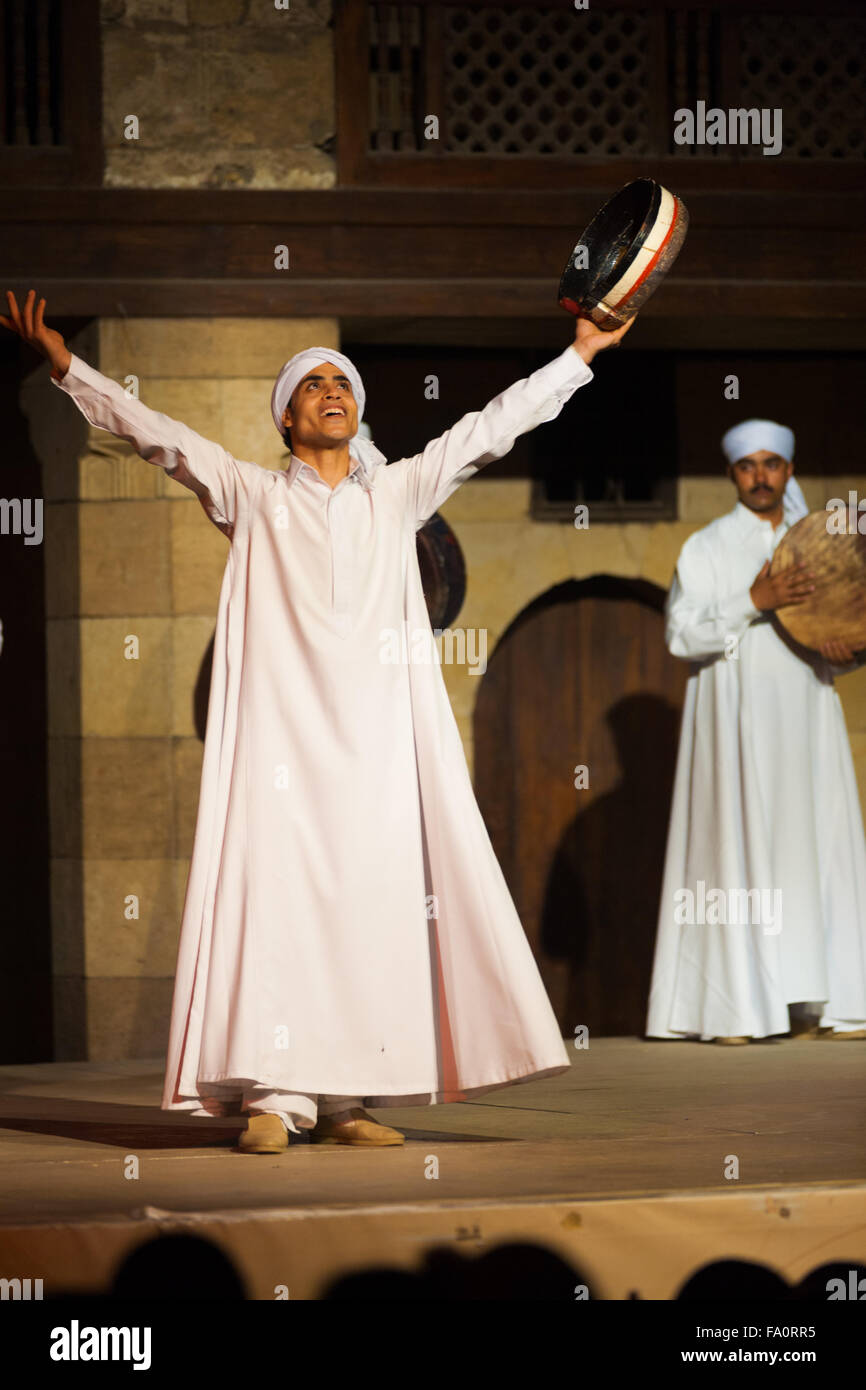 A Sufi dancer in white holding tamborine raising his arms after whirling dervish at an open air courtyard performance - Stock Image