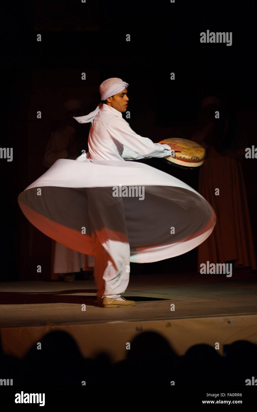 A Sufi dancer in white spins and beats a drum during a whirling dervish at an open air courtyard performance at - Stock Image