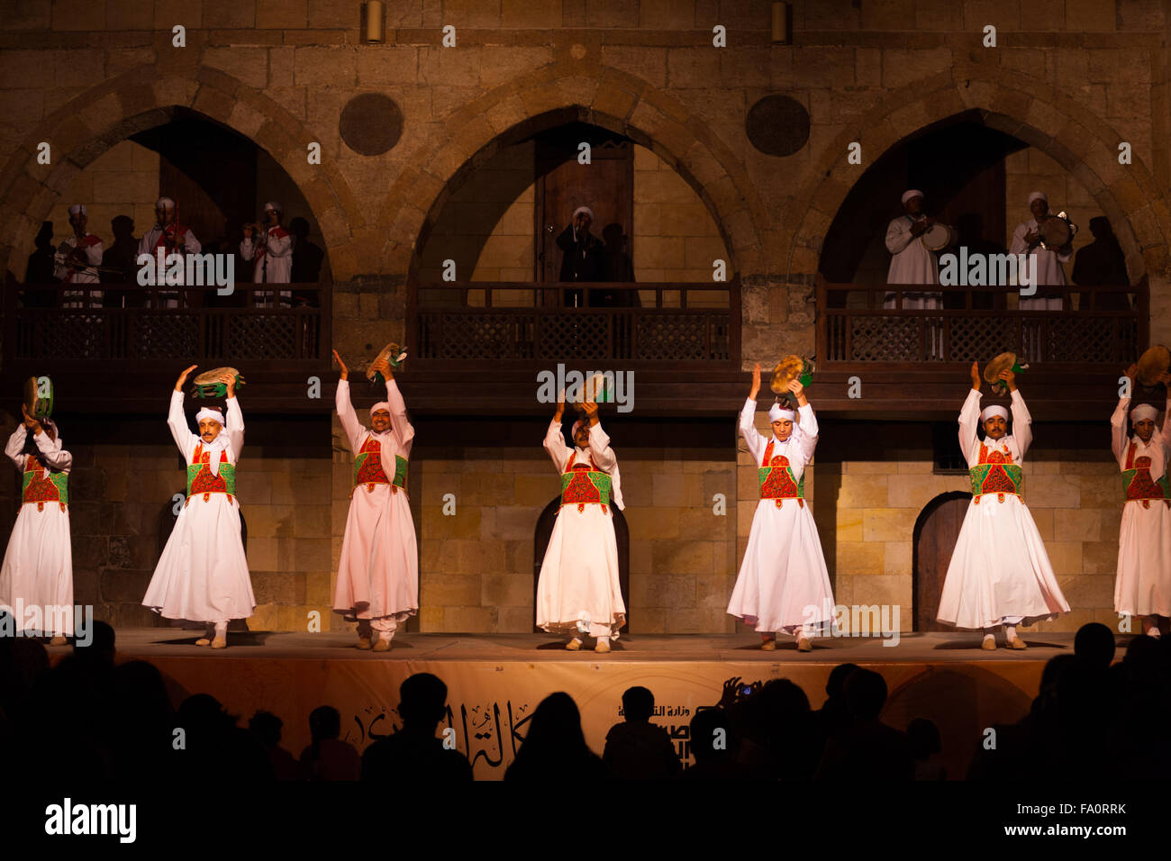 A row of Sufi dancers in white play tamborines during a whirling dervish performance at the Al Ghouri courtyard - Stock Image