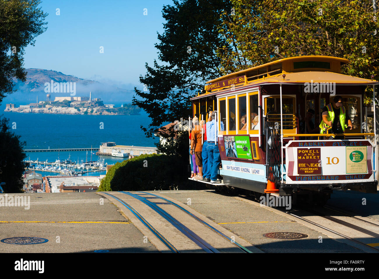 Powell Hyde cable car, an iconic tourist attraction, descending a steep hill peak overlooking Alcatraz prison island - Stock Image