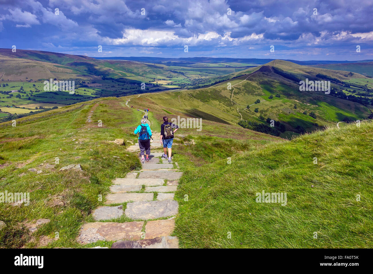 Hikers on the flagged footpath along the Great Ridge above Castleton, Peak District Derbyshire Stock Photo