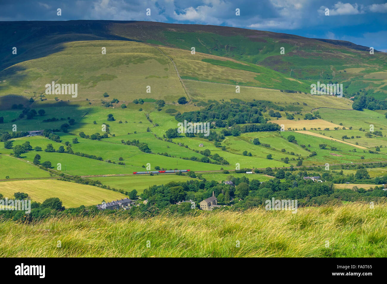 Small red train passing below Kinder Scout moors, Edale, - Stock Image