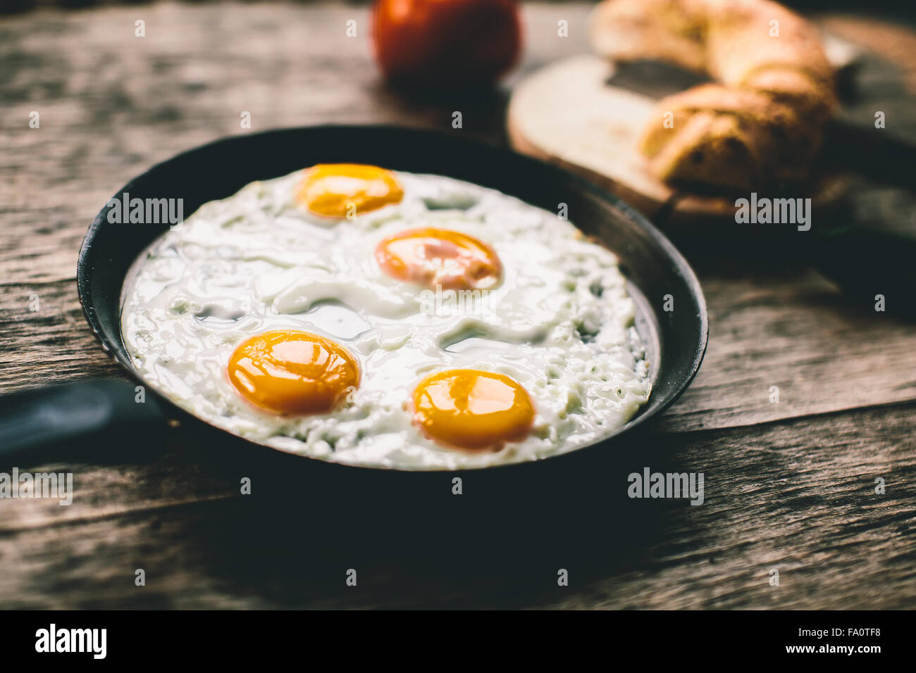 Fried egg in a frying pan on a wooden table - Stock Image