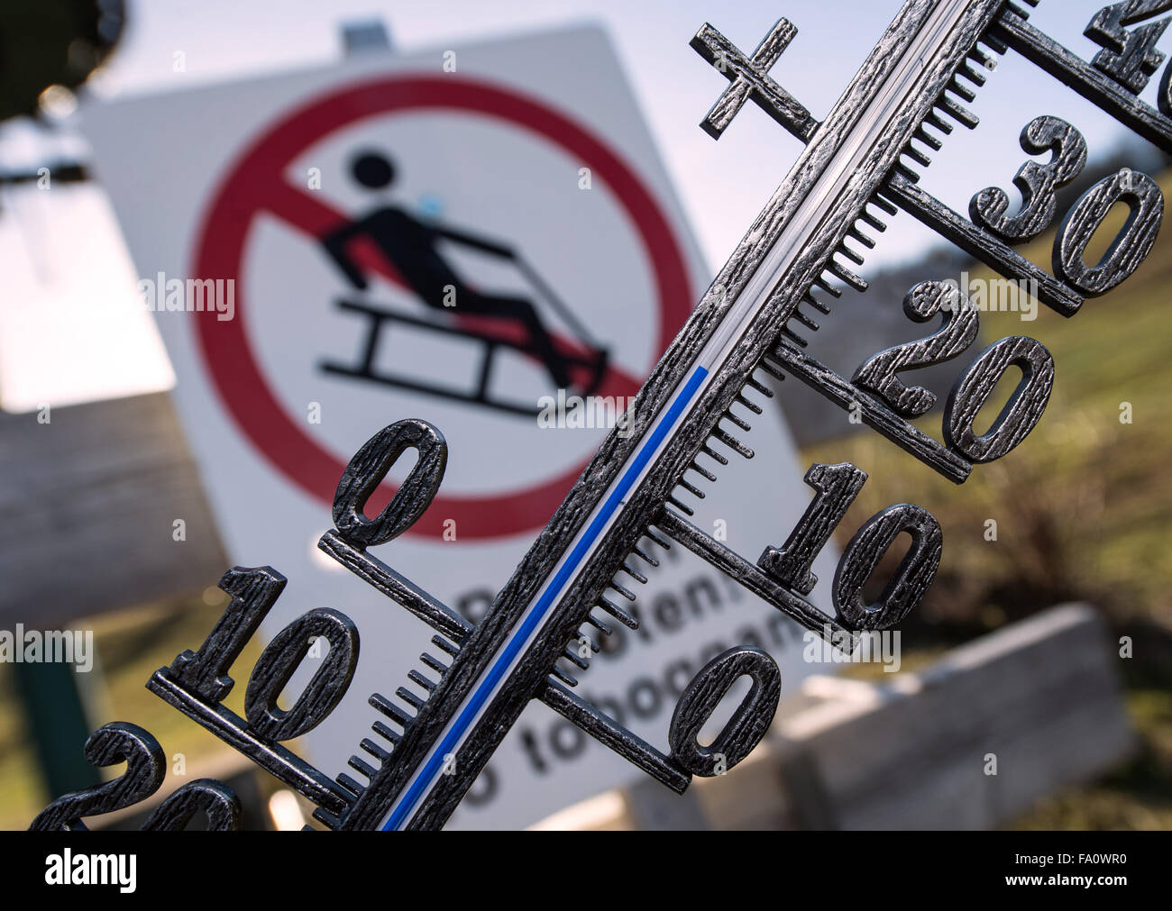 ILLUSTRATION - A thermometer measures nearly 18 degrees Celsius in front of a sign that prohibits bobsleighing near - Stock Image