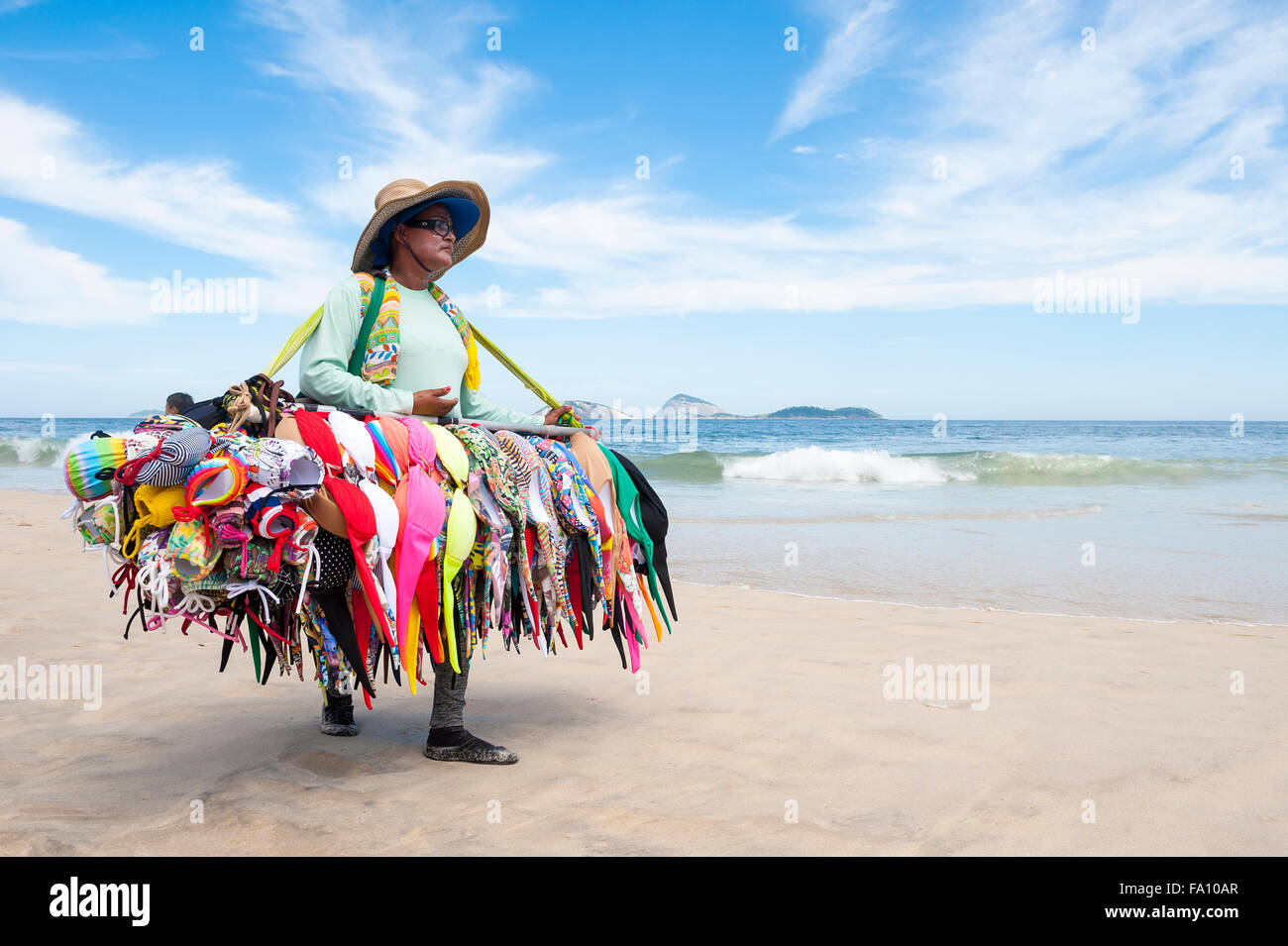 RIO DE JANEIRO, BRAZIL - MARCH 15, 2015: A beach vendor selling bikinis carries her merchandise along Ipanema Beach. - Stock Image