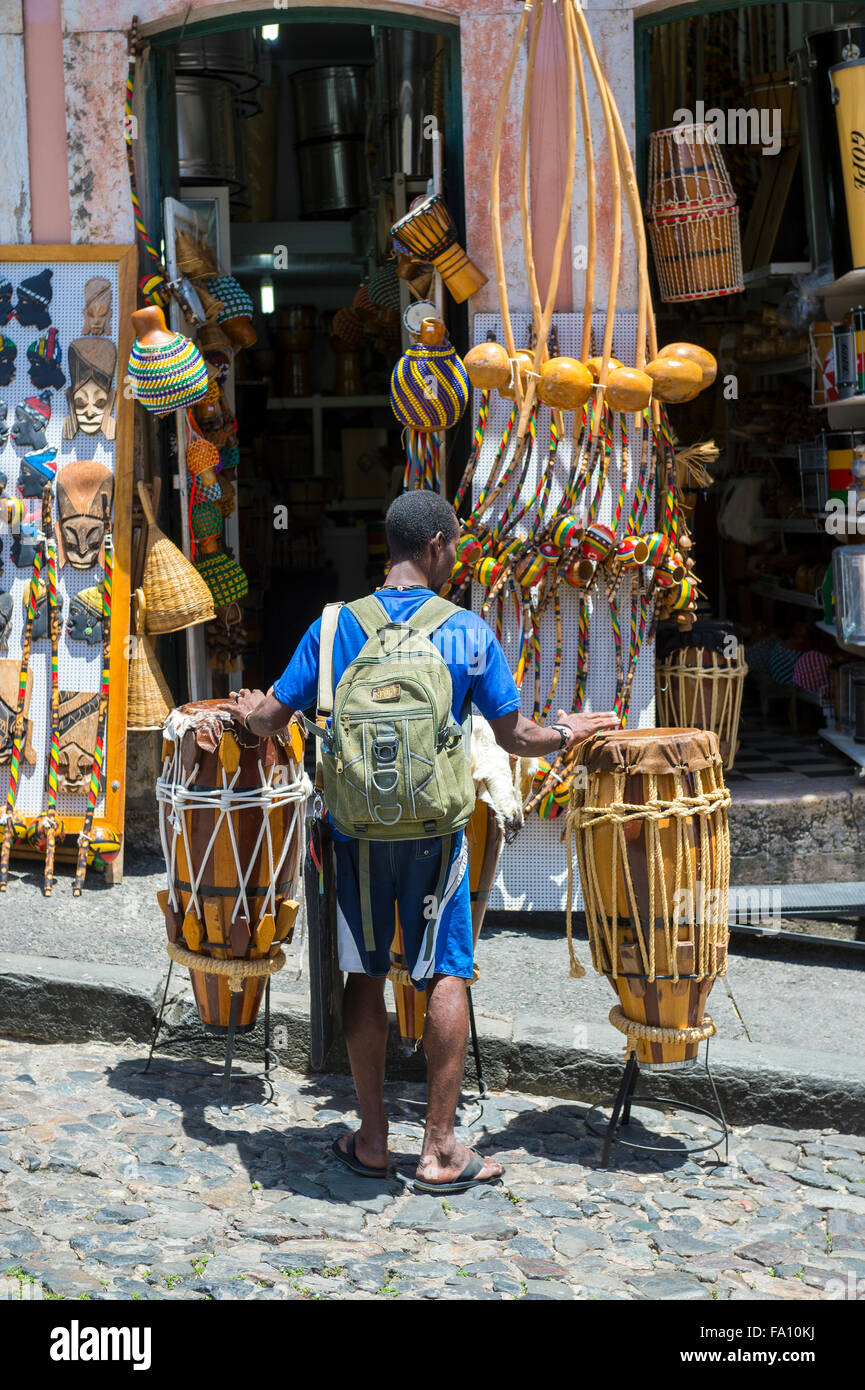 SALVADOR, BRAZIL - MARCH 12, 2015: Brazilian street performer walks with rustic pair of drums in the Pelourinho - Stock Image