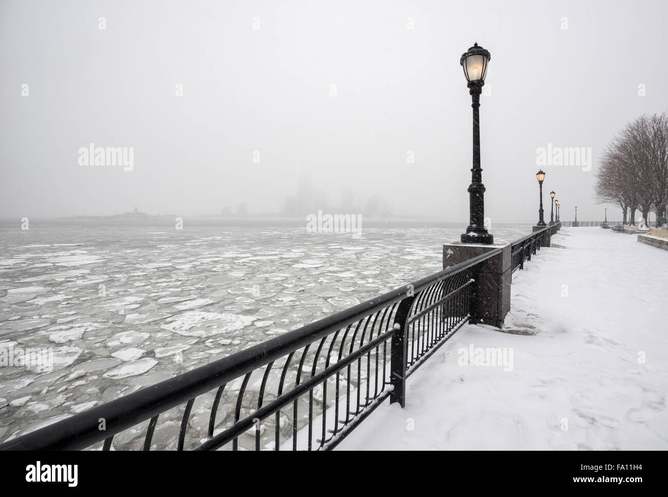 Frozen Hudson River from snowy Battery Park towards Jersey City in fog. A silent winter day in New York City - Stock Image