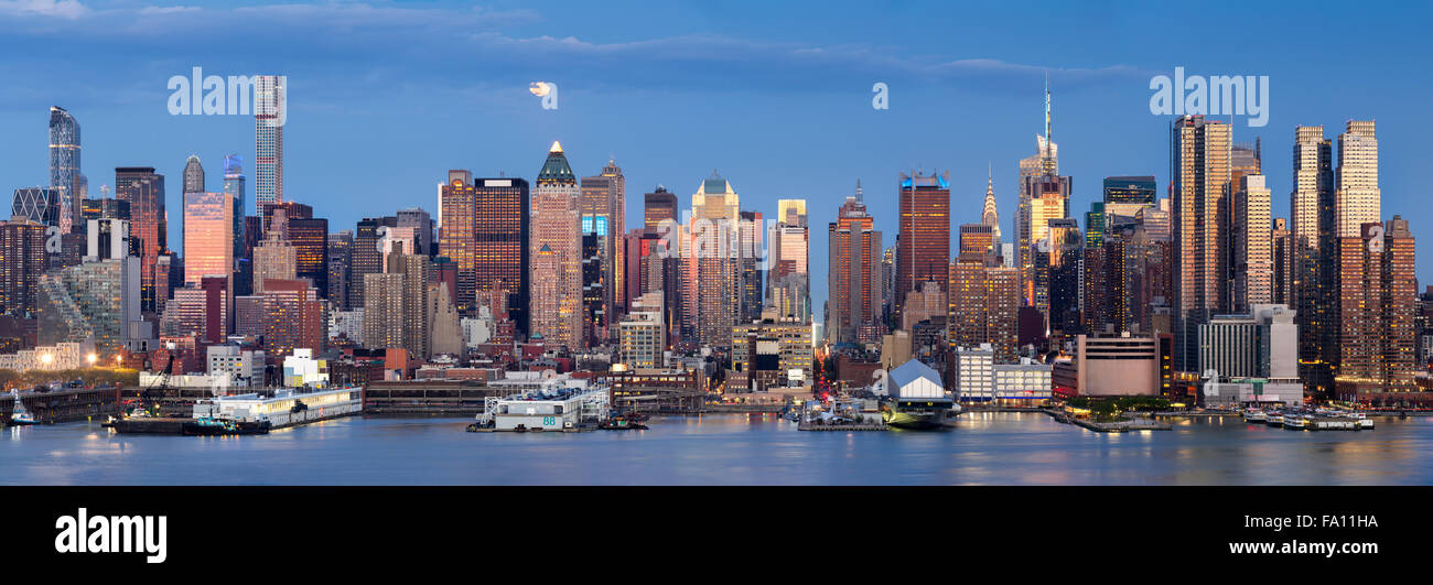 Midtown West Manhattan skyscrapers & the Hudson River. Panoramic view in early evening with moonrise and New - Stock Image