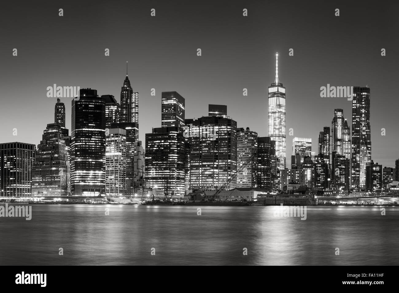 Black & White East River view of Financial District skyscrapers at dusk. Illuminated Lower Manhattan skyline, New Stock Photo