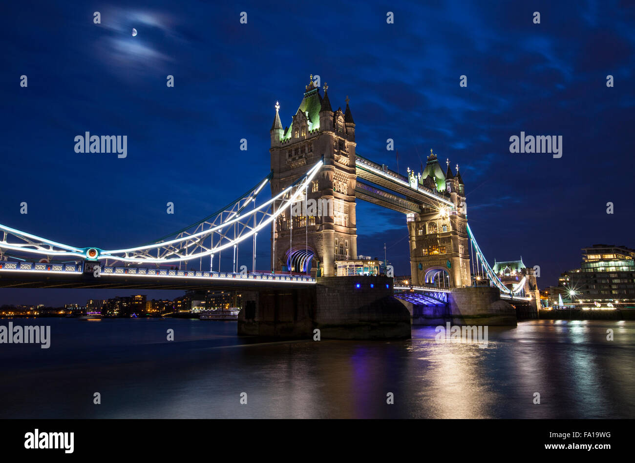 A dusk-time view of the magnificent Tower Bridge spanning over the River Thames in London. - Stock Image