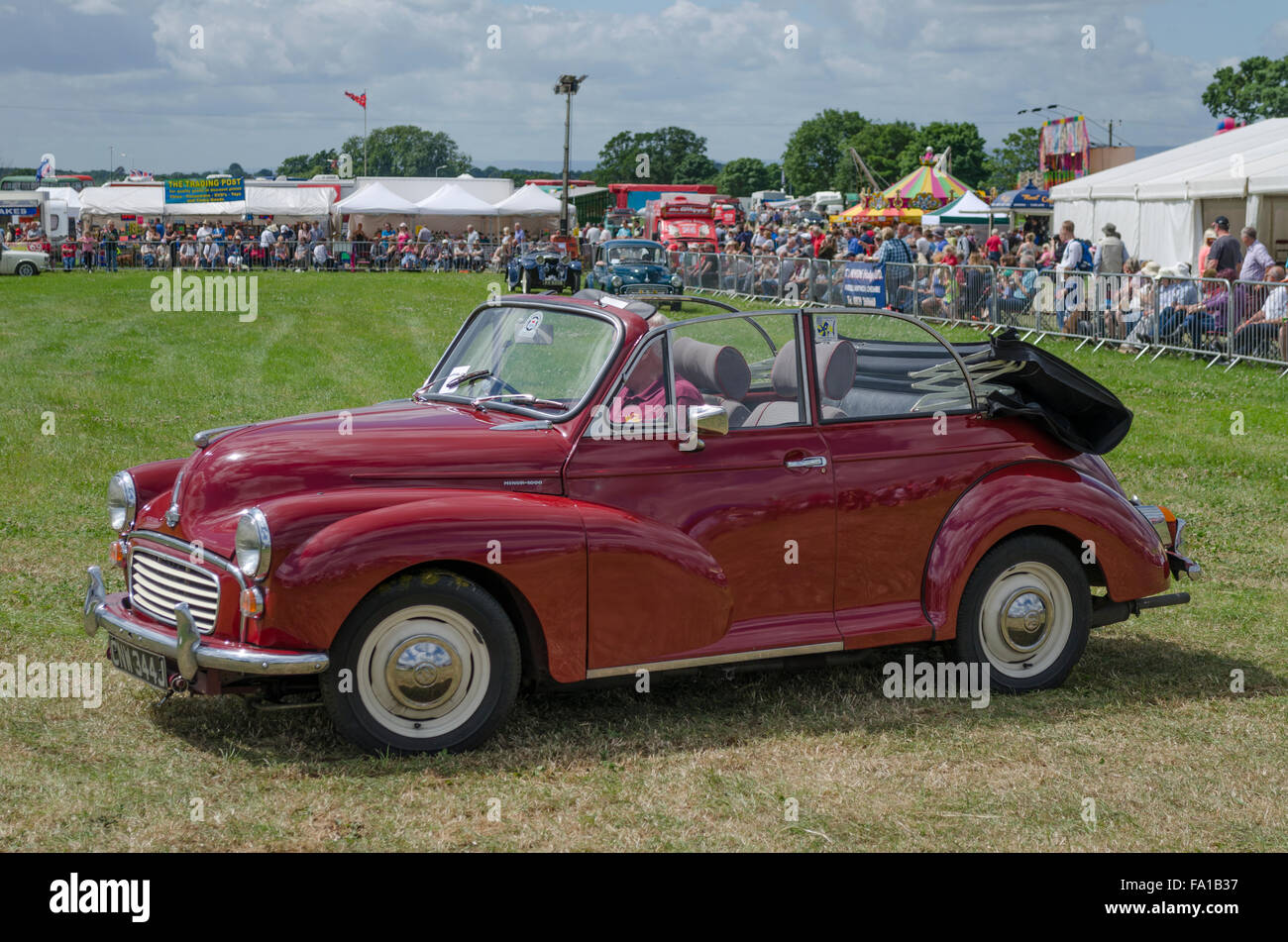 Maroon 1971 Morris Minor convertible  being driven around a parade ground at a classic car show - Stock Image