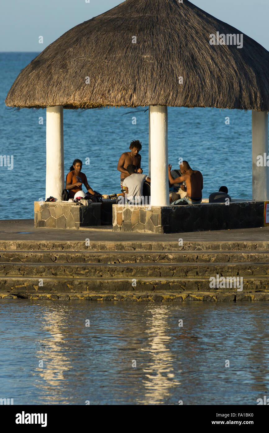 Local Mauritians gathering by the sea to play music and socialise - Stock Image