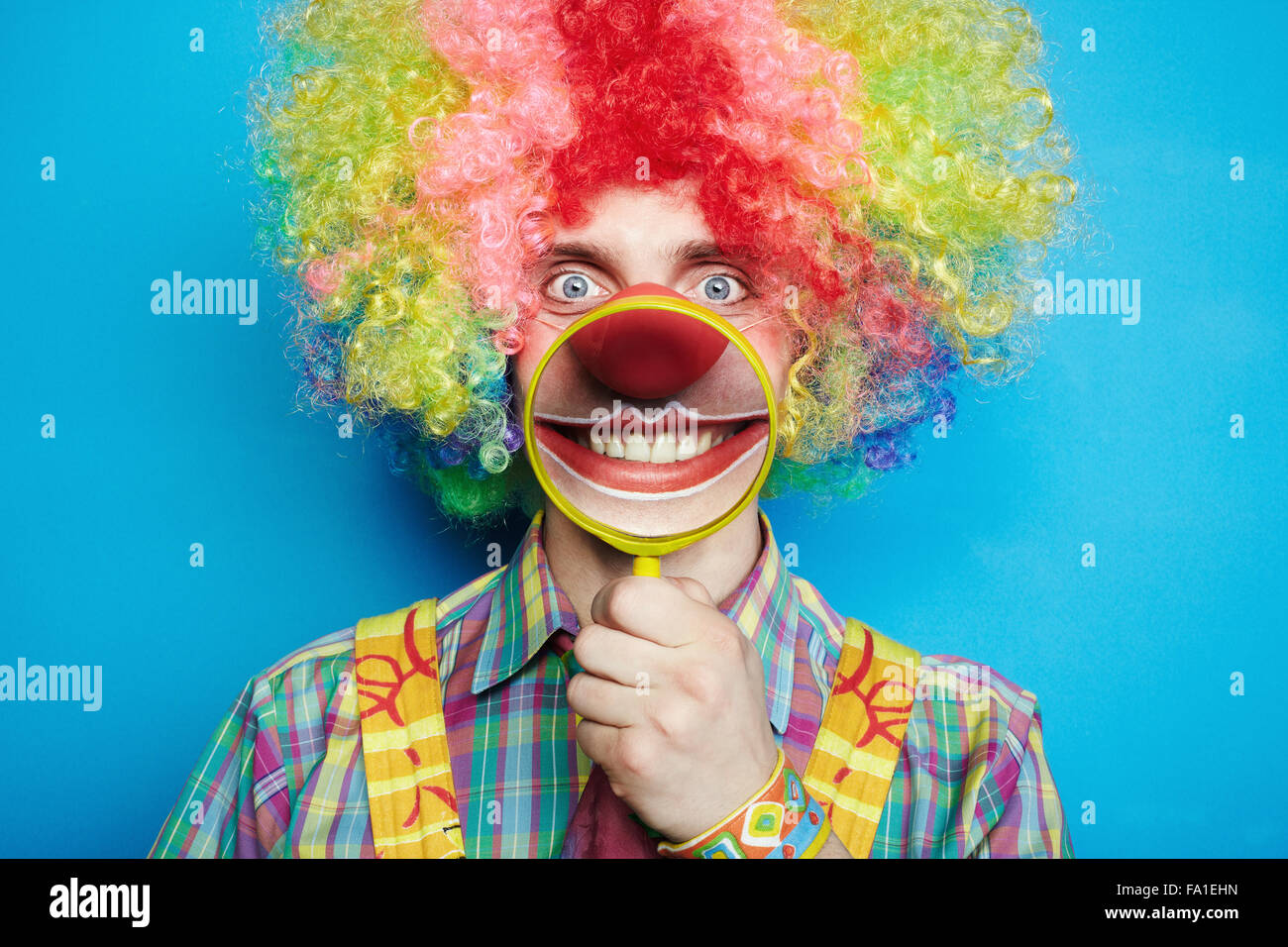 Portrait cheerful clown with the big smile on a blue background - Stock Image