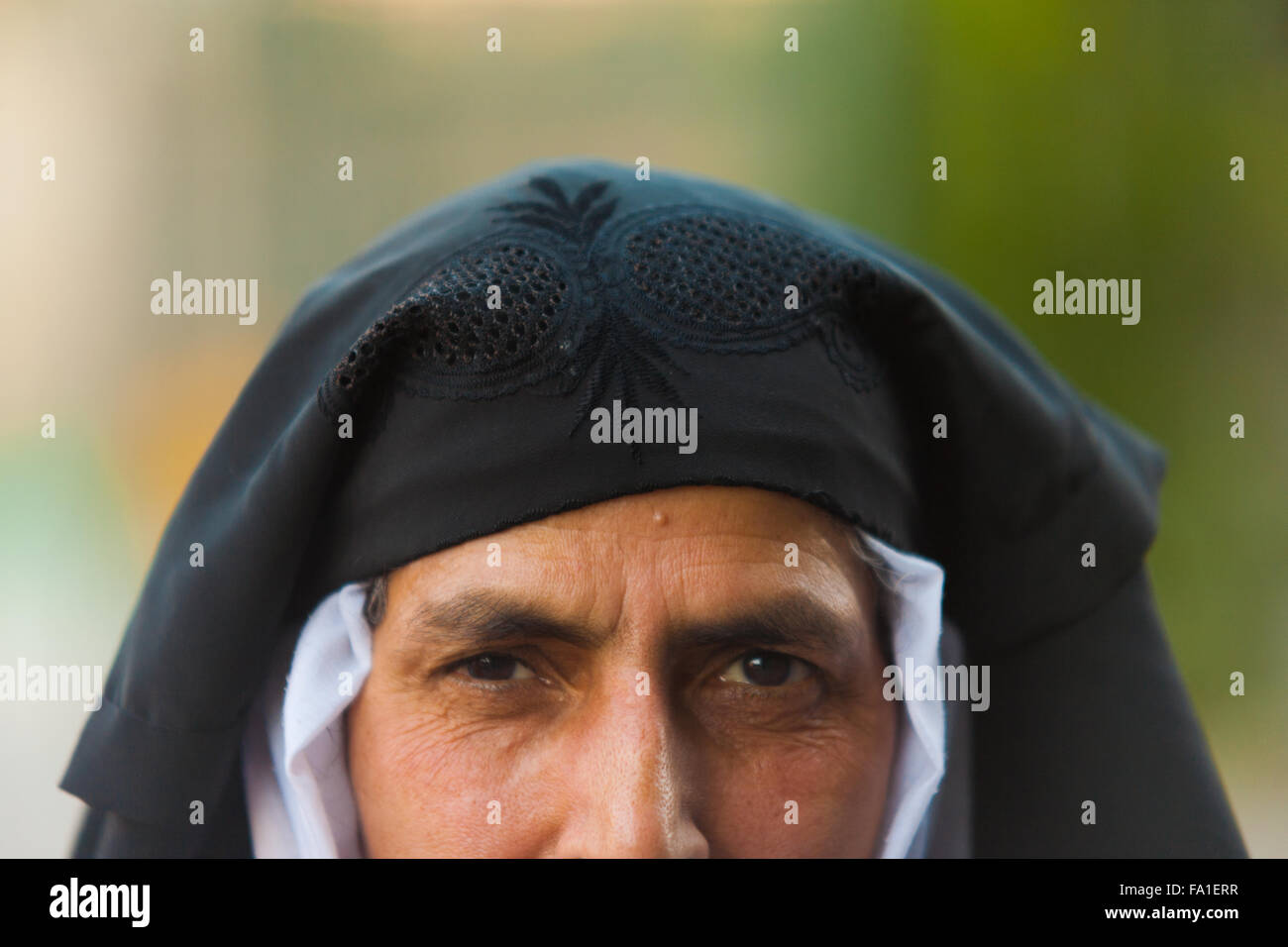 Half face portrait of Kashmiri muslim woman wearing pulled back black niqab full face veil exposing her face and - Stock Image