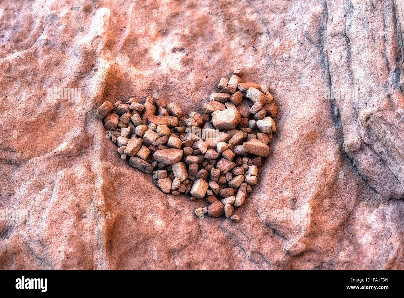 Small rocks formed into the shape of a heart. - Stock Image