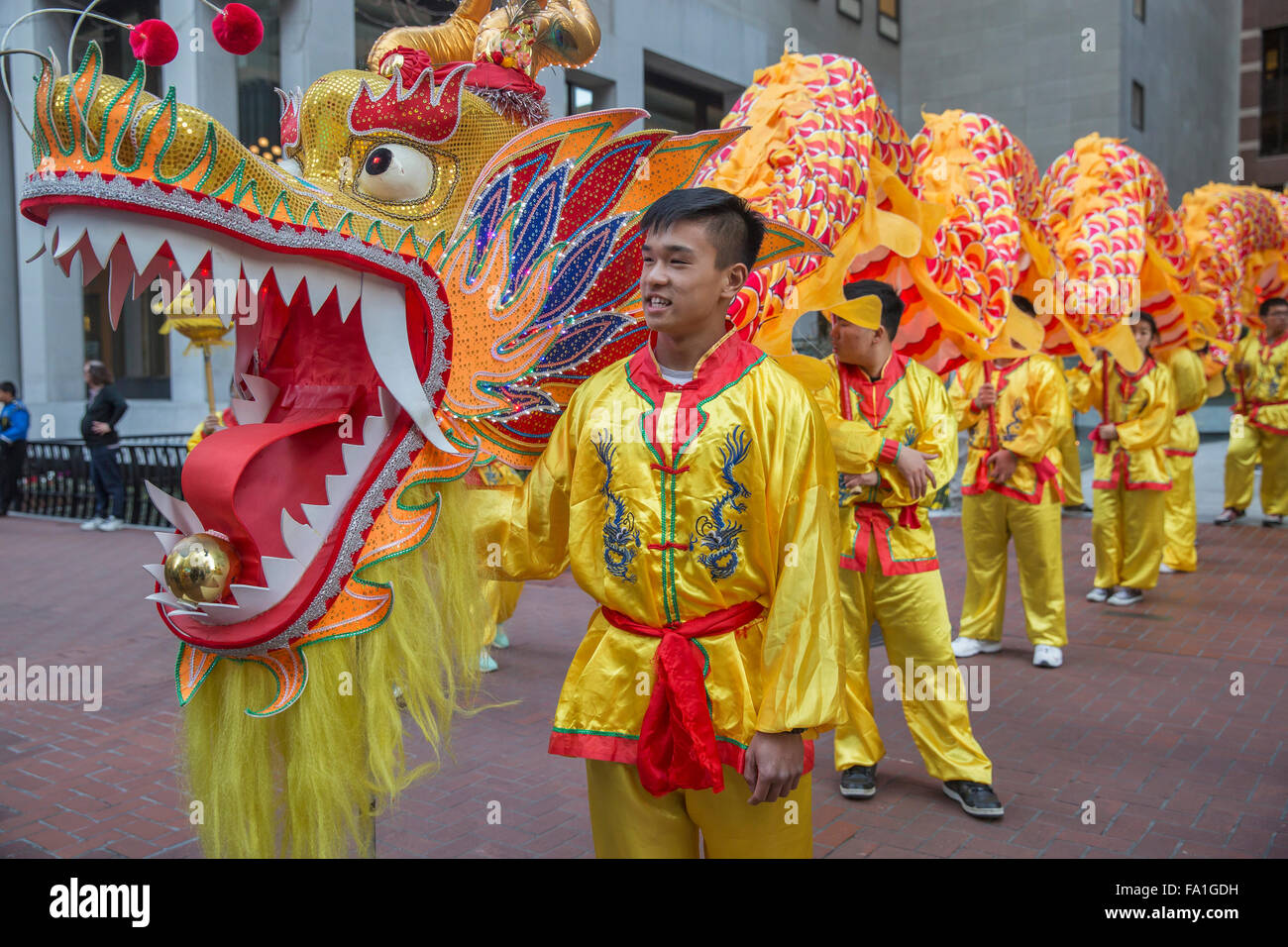 Dragon handlers dressed in colorful costumes at San Francisco Chinese New Year parade. - Stock Image