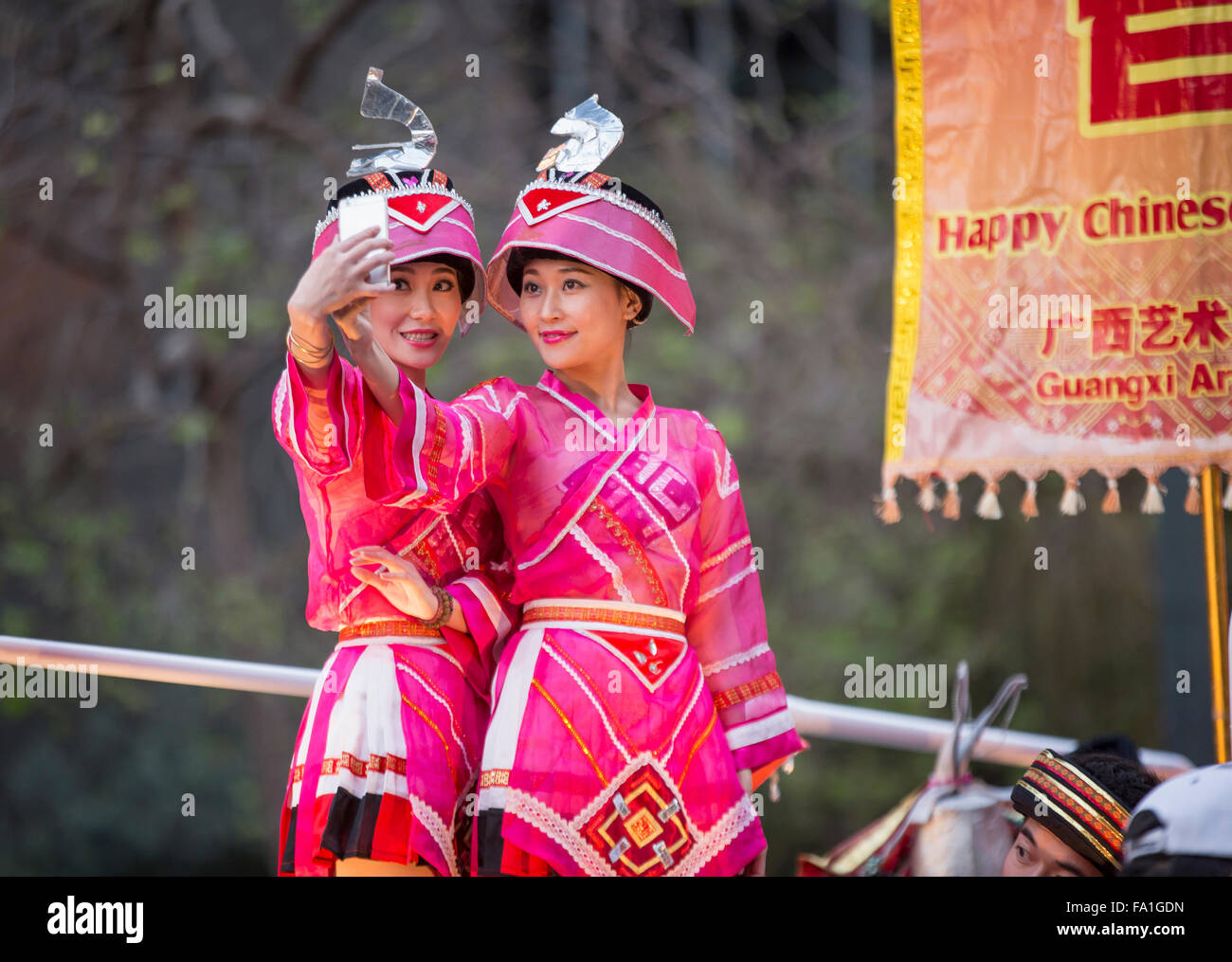 Chinese women dressed in colorful costumes taking a selfie atop float at San Francisco Chinese New Year parade. - Stock Image