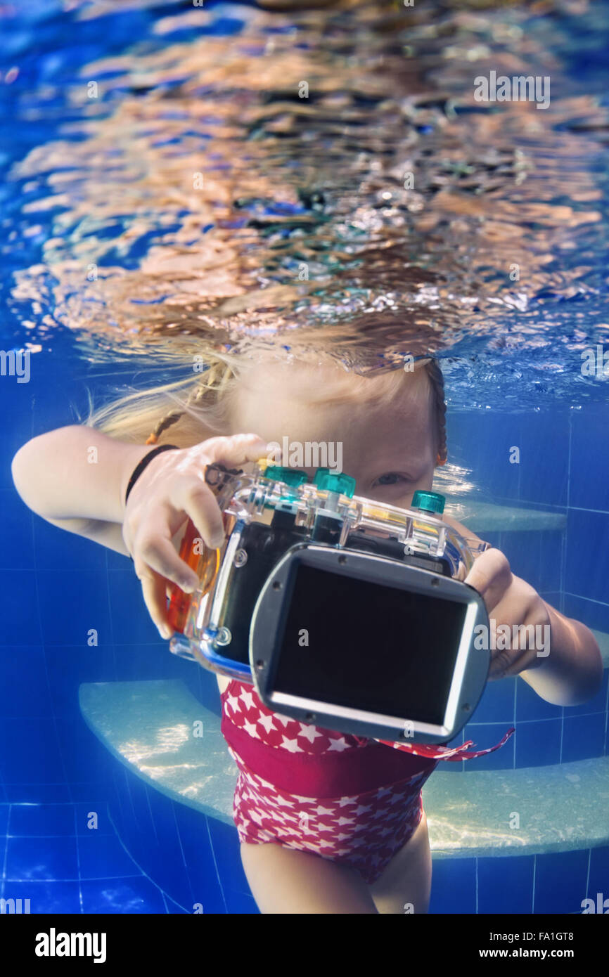 Little baby photographer with camera swim and dive with fun to take funny underwater photo of parent in blue pool. - Stock Image