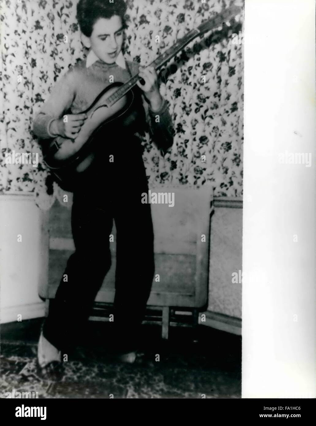 1955 - childhood At home in Liverpool - 13 years ago - George Harrison plays his first guitar, his age? 12. © - Stock Image
