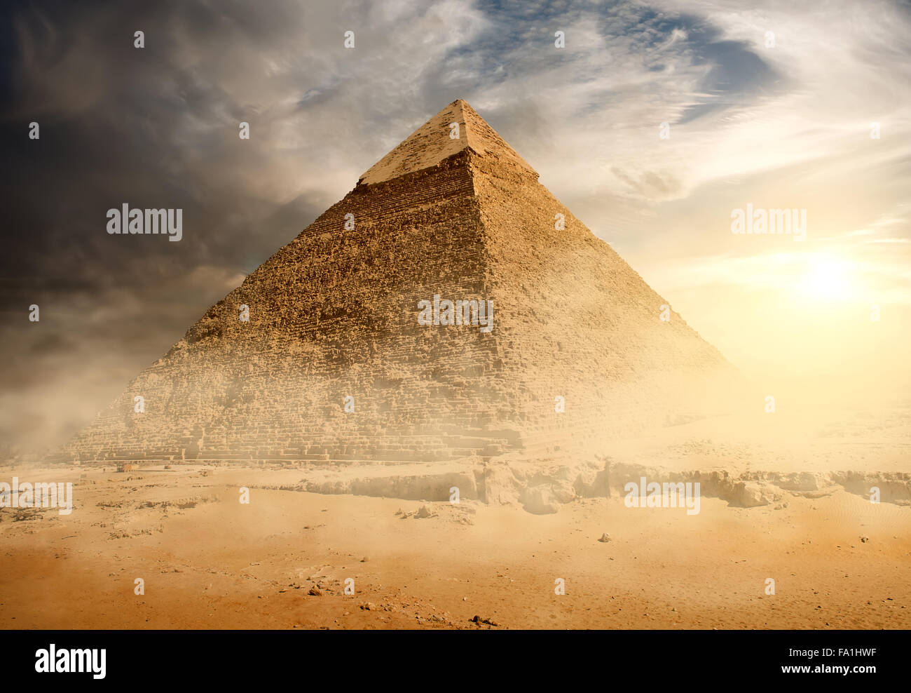 Pyramid in sand dust under gray clouds - Stock Image