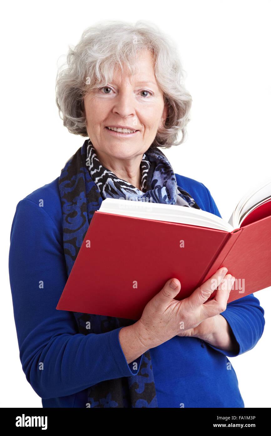Elderly female teacher reading a red book aloud - Stock Image