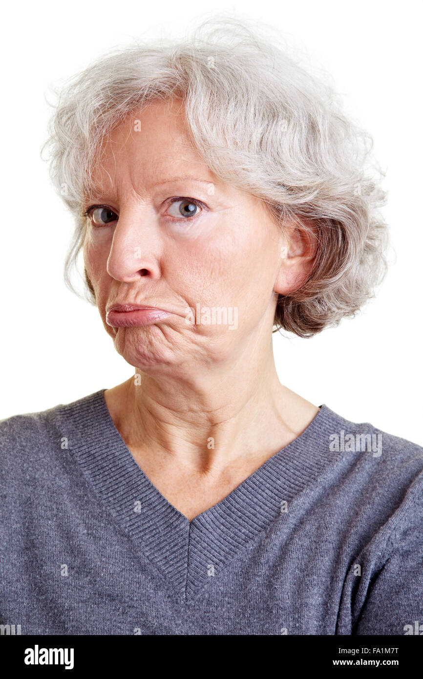 Old senior woman grimacing with her face - Stock Image