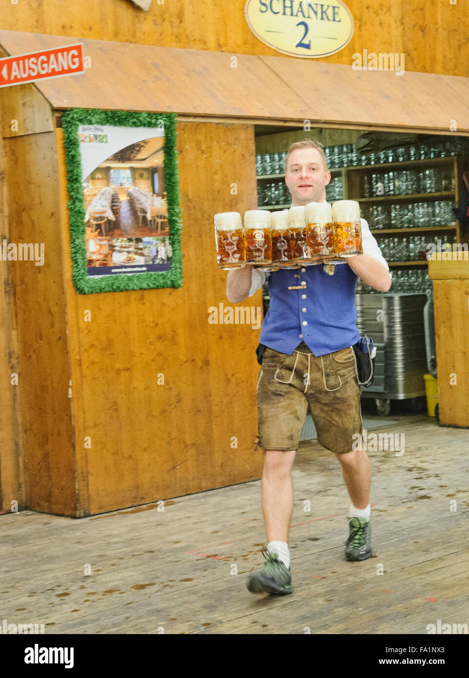 Waiter in a traditional lederhosen carrying giant glasses of beers in Oktoberfest in Munich, Germany - Stock Image