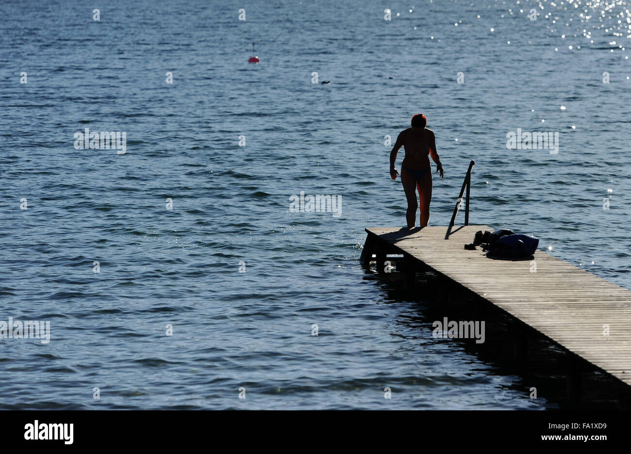Gmund, Germany. 20th Dec, 2015. A woman climbs onto a jetty after swimming in sunny weather at Tegernsee lake near - Stock Image