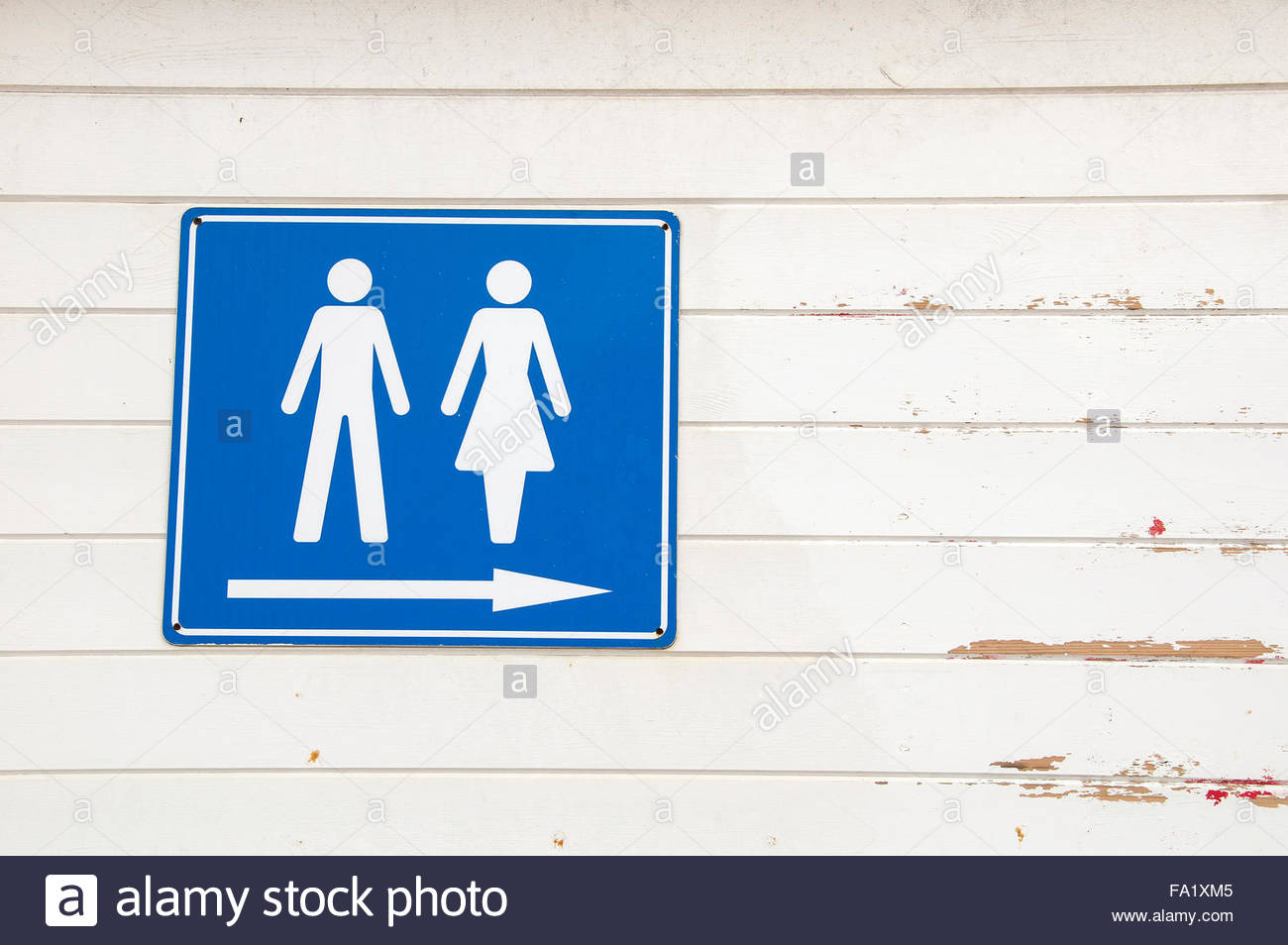A Blue And White Male Female Toilet Sign With Arrow Pointing To The Right