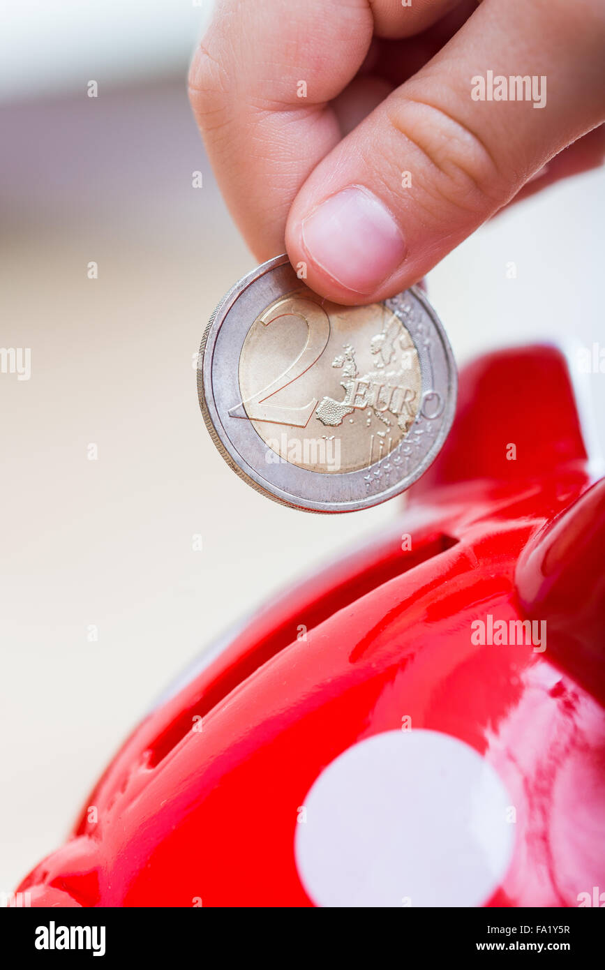 child thrown into Piggy coin - two euro - Stock Image