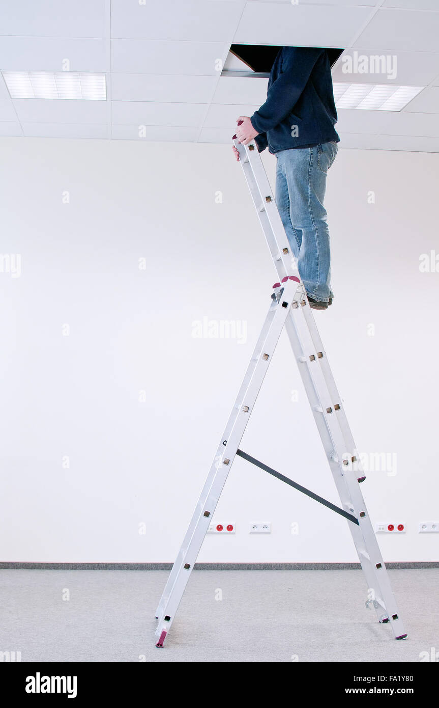 worker on a ladder, peering through a hole in the ceiling - Stock Image