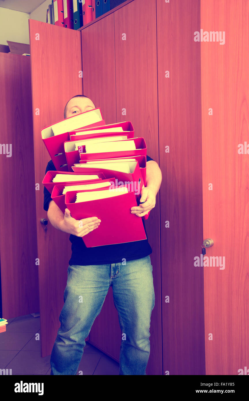 Man carrying folders with documents - too many documents at once - Stock Image