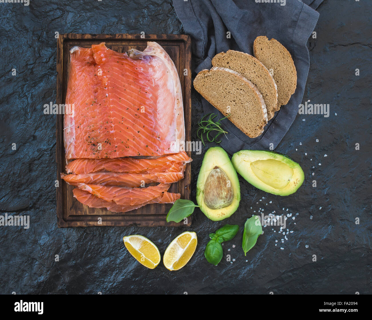 Smoked salmon filet with lemon, avocado, fresh herbs and bred on wooden serving board over dark stone backdrop, - Stock Image