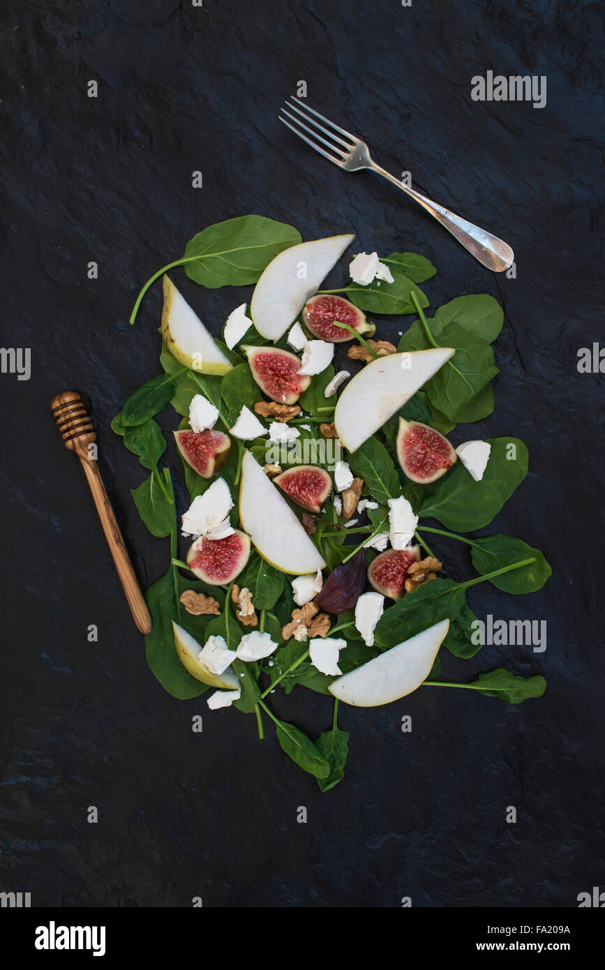 Salad with pears, baby spinach, figs, walnuts, goat cheese and honey on black stone background, top view - Stock Image