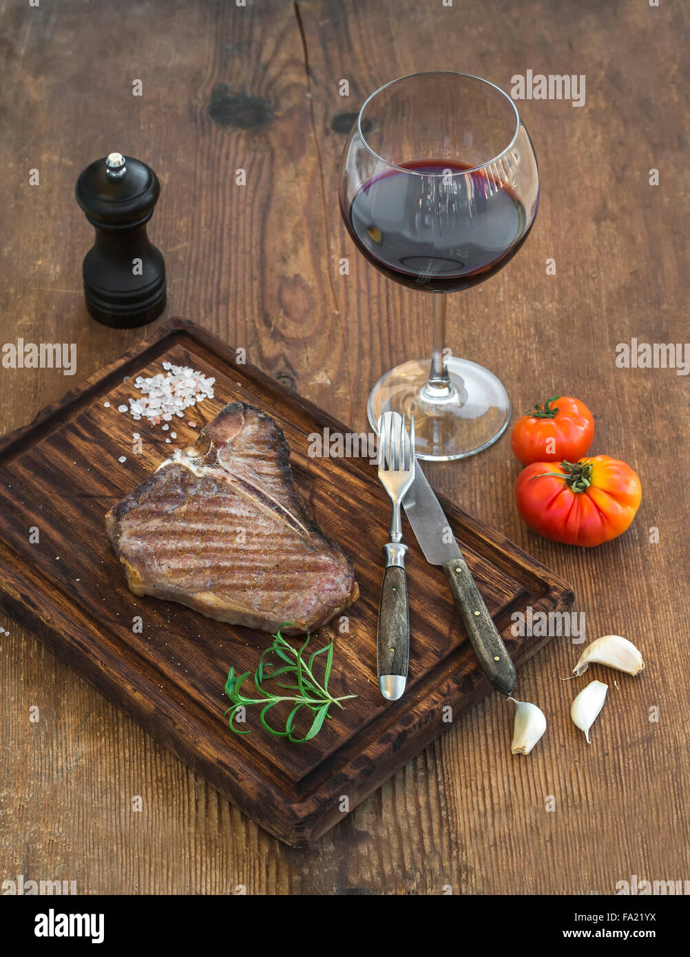Cooked meat t-bone steak on serving board with garlic cloves, tomatoes, rosemary, spices and glass of red wine over Stock Photo