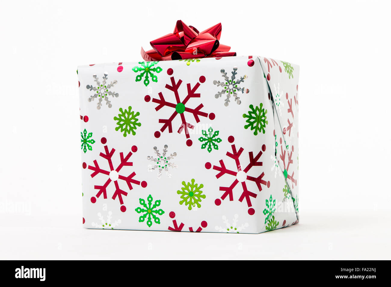 Christmas gift, wrapped in paper featuring snowflakes - Stock Image
