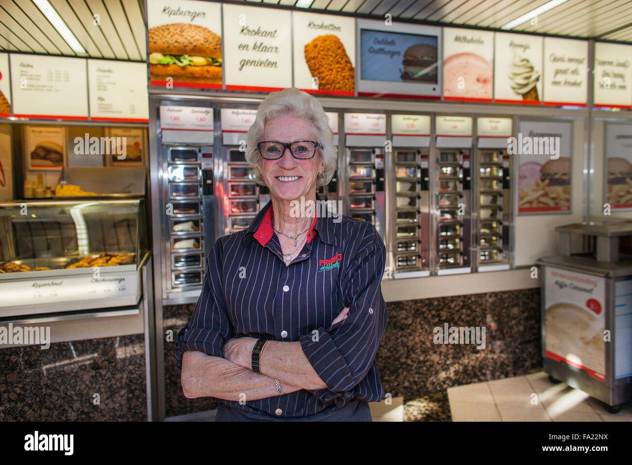 Yvonne Blom (72), owner of fast Food restaurant FEBO in Holland. Clients can 'pull food from a wall'. - Stock Image