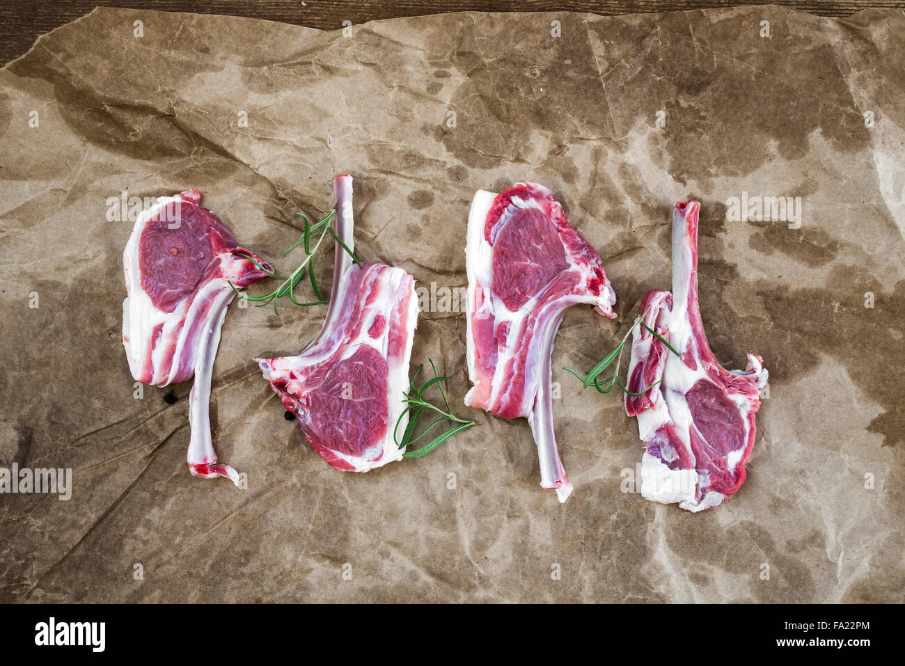 Raw lamb chops. Rack of Lamb with rosemary and spices over oily craft paper background, top view - Stock Image