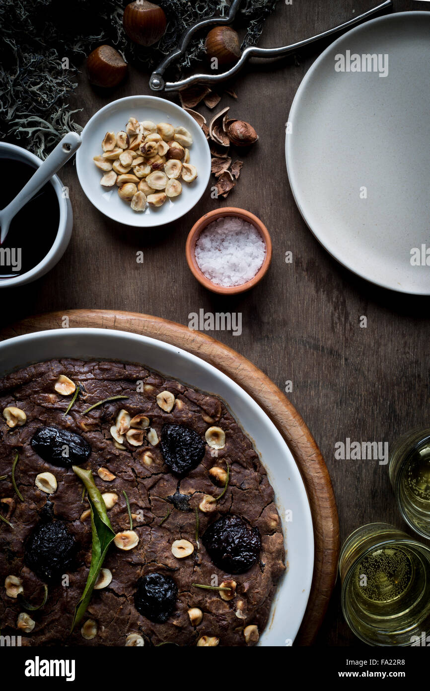 Festive Mediterranean Chestnut Flour Cake in white dish on set wooden table with ingredients, Christmas decoration, - Stock Image