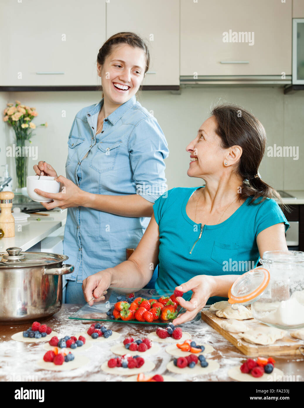 Two smiling women making perogies with berries at home kitchen Stock ...