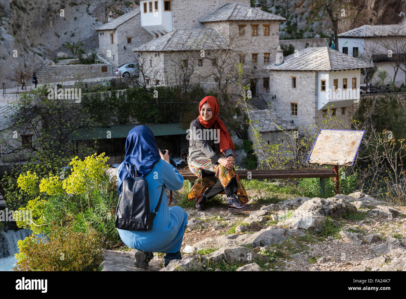 A young woman takes a picture of her friend near the Blagaj Tekke on April 16, 2015 in Blagaj, Bosnia and Herzegovina. - Stock Image