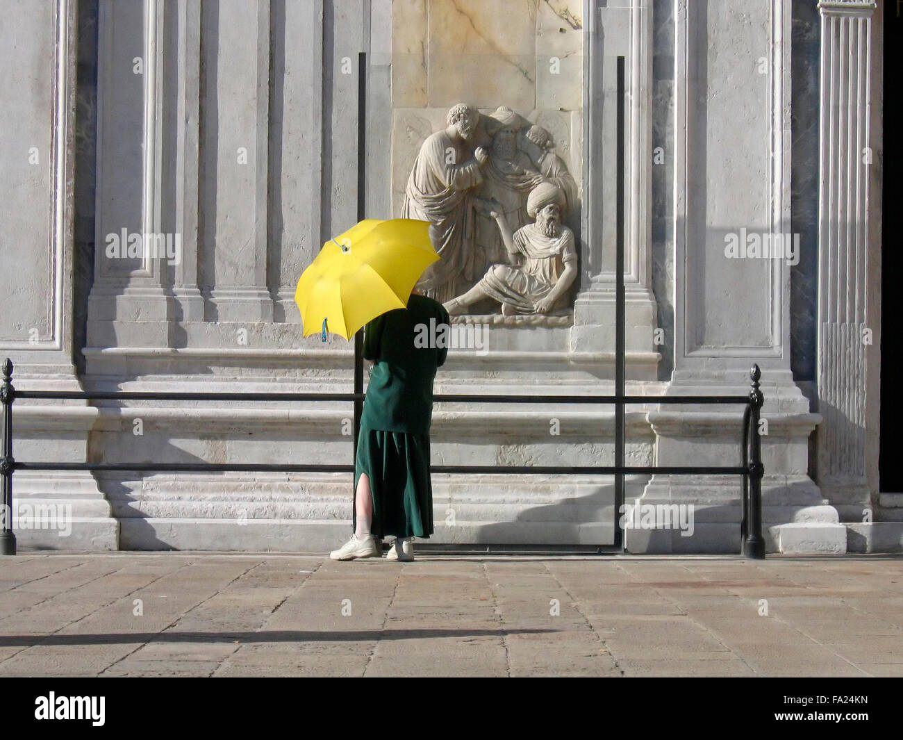 Lady with yellow umbrella watching statues in Venice,Italy - Stock Image